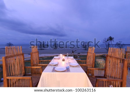 romantic twilight dinner with wooden chairs and tables setting near beach - stock photo