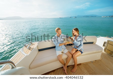 Romantic vacation and luxury travel. Young loving couple sitting on the sofa on the modern yacht deck. Sailing the sea.