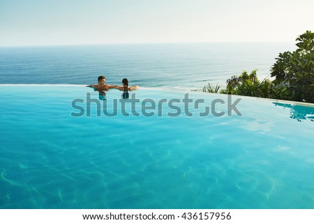Romantic Vacation For Couple In Love. Happy People Relaxing In Infinity Edge Swimming Pool Water, Enjoying Beautiful Sea View. Man, Woman Together On Summer Travel To Luxury Resort. Summertime Relax - stock photo