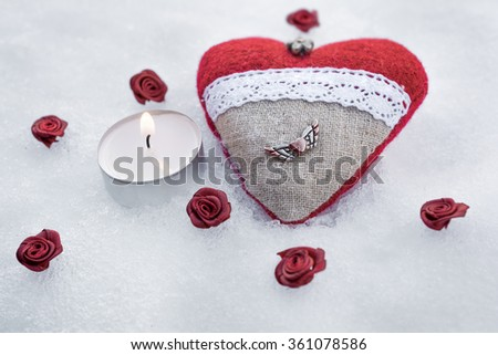 Romantic Valentine Plush Heart With A Winged Metal Heart On Ice Besides A Peaceful Tea Light Surrounded By Rose Bloom - stock photo