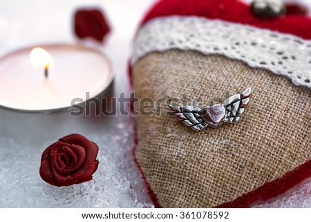 Romantic Valentine Plush Heart With A Winged Metal Heart On Ice Besides A Peaceful Tealight Surrounded By Rose Bloom - stock photo