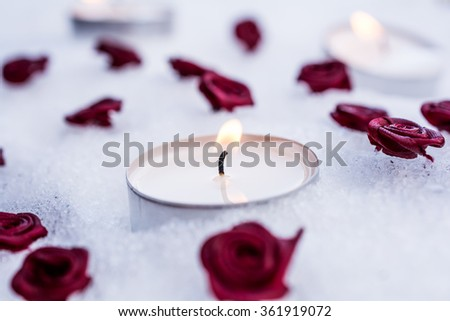 Romantic Valentine Tealights On Snow Surrounded By Rose Bloom - stock photo