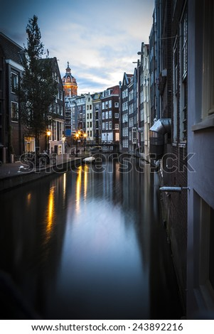 Romantic view of Amsterdam: canal in the Red District. Buildings and street lamps are reflected in the water  - stock photo