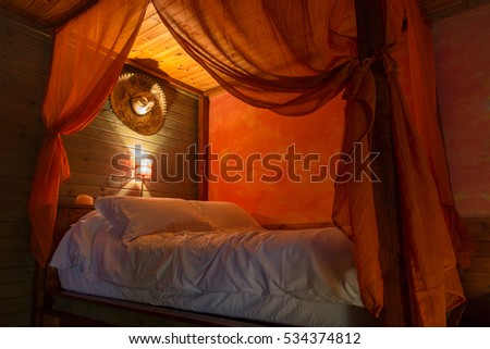 romantic view of the bed with red light  in a wooden house
