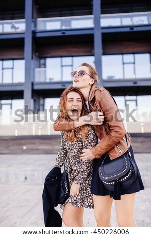 Romantic walk of two stylish girlfriend. One girl with unbounded red hair is wearing motley dress. She is smiling to her friend. Another girl is wearing brown leather jacket and short black skirt. - stock photo