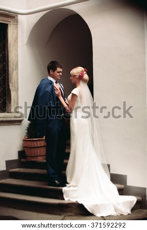 Romantic wedding couple, man and wife, posing near old building column