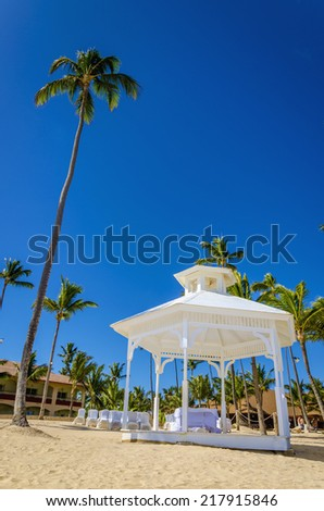 Romantic white gazebo in the exotic Caribbean beach with tall palm trees