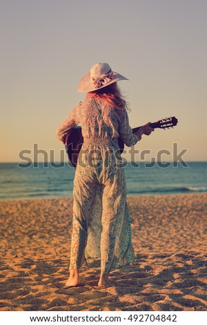Romantic woman on seashore sunset walk outdoors background. Back view