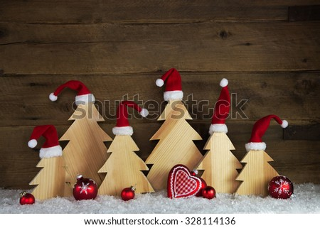 Romantic wooden christmas background with red santa hats and crafted trees. - stock photo