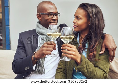 Romantic young African American couple share a toast clinking their glasses of white wine as the look deeply into each others eyes - stock photo