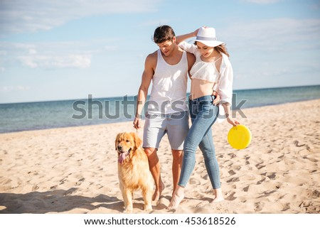Romantic young beautiful couple walking on the sea shore with dog