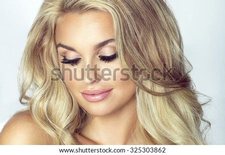Romantic young blonde woman with closed eyes. Fashion photo. Girl with long healthy hair and perfect makeup. Studio shot. - stock photo