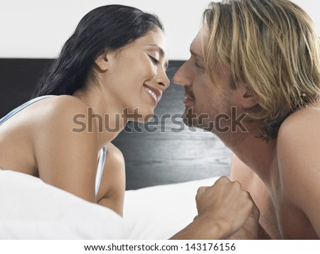 Romantic young couple about to kiss on bed in hotel room - stock photo