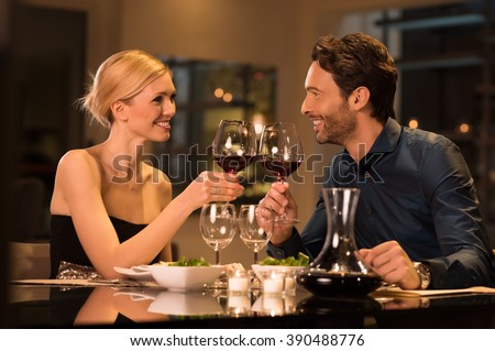 Romantic young couple at restaurant raising a toast. Beautiful couple with glasses of red wine in restaurant. Couple toasting wine glasses during a romantic dinner in a gourmet restaurant. - stock photo