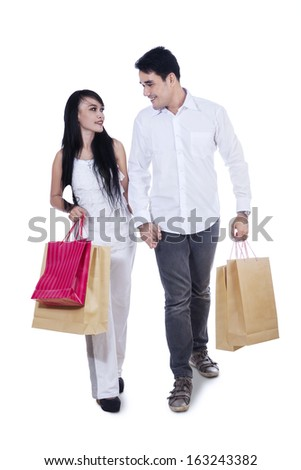 Romantic young couple carrying shopping bags isolated on white background  - stock photo