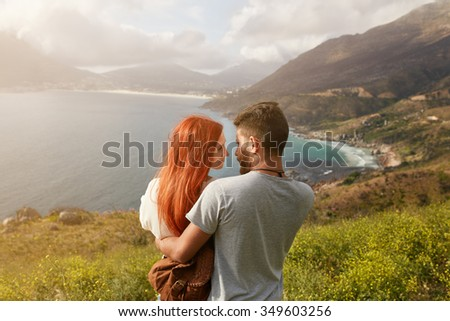 Romantic young couple embracing and looking at each other on a sunny day outdoors. Man and woman looking into each others eyes affectionately.