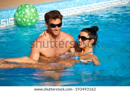 Romantic young couple having fun in swimming pool, enjoying holiday, smiling.