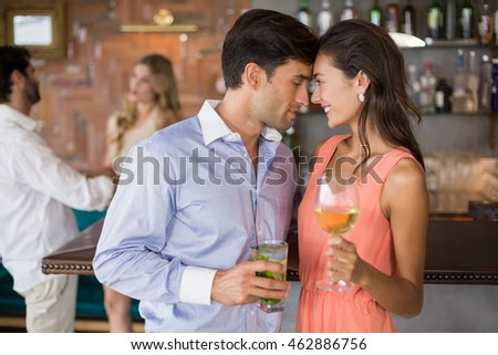 Romantic young couple holding wine glasses in restaurant