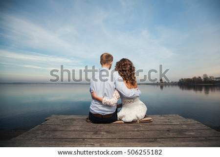 Romantic young couple hugging sitting by the lake on a wooden wharf and looking into the distance, love, relationship, family, couple hugging  from back