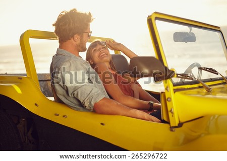 Romantic young couple in a car. Young woman looking at her boyfriend smiling. Couple on a road trip on a summer day. - stock photo