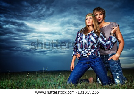 Romantic young couple in casual clothes sitting together in a field on a background of the storm sky. - stock photo