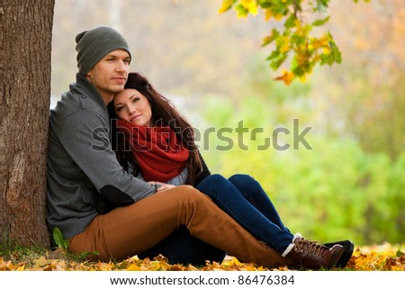 Romantic young couple in love relaxing outdoors in park - stock photo