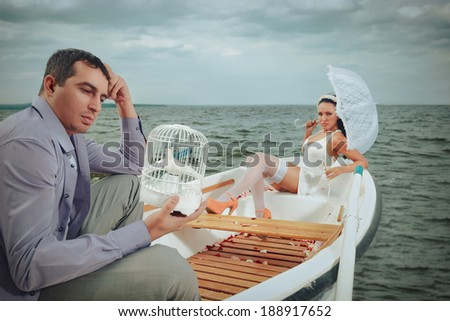 Romantic young couple in rowboat at lake - stock photo