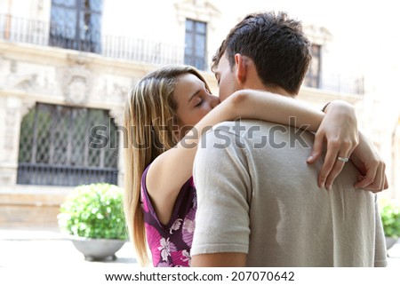 Romantic young couple kissing each other with passion in a city street during a sunny day on holiday, outdoors. (People, Lifestyle, Romance) - stock photo