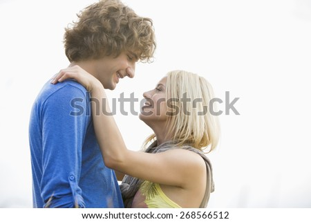 Romantic young couple looking at each other against clear sky - stock photo