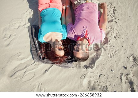 Romantic young couple lying on the beach on a warm sunny day - stock photo