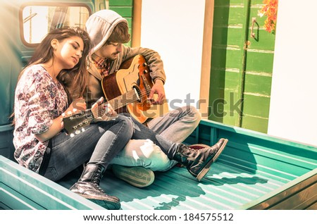 Romantic young Couple of lovers playing Guitar outdoor after the Rain - stock photo