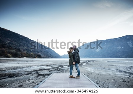 Romantic young couple on a pier holding hands, lake and mountains on background - stock photo