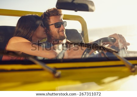 Romantic young couple sharing a special moment while on a road trip. Man driving car with girlfriend. - stock photo
