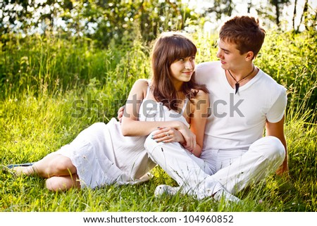 Romantic young couple sitting in a field - stock photo