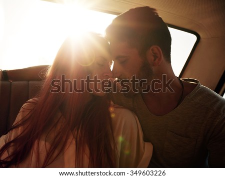 Romantic young couple sitting in back seat of a car. Young couple feeling romantic in back seat of a vehicle with sun flare from behind. - stock photo