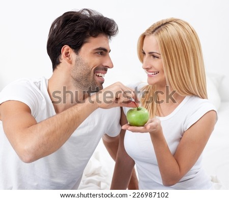 Romantic young couple sitting in bed at home in the morning. Sharing an apple.