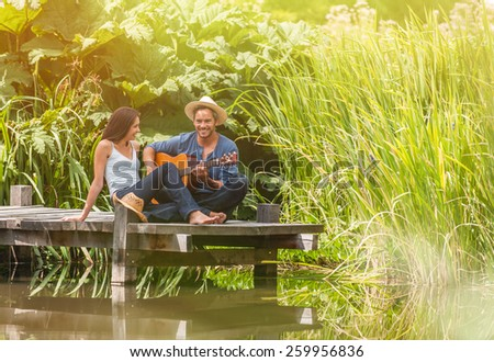 romantic young couple sitting on a wood pontoon near a river, man playing guitar and he wears a straw hat - stock photo