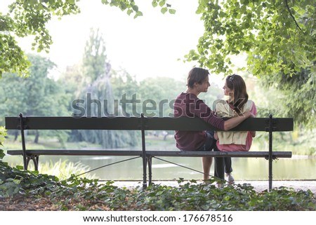 Romantic young couple sitting on park bench by lake - stock photo