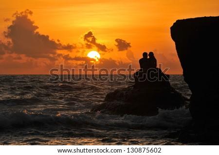 Romantic young couple sunset silhouette on beach. honeymoon - stock photo