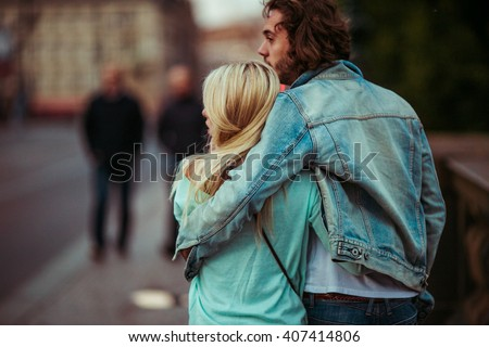 Romantic young couple walking & hugging in Prague street - stock photo