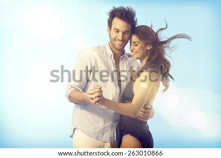 Romantic young loving couple dancing outdoors under blue sky at summertime.