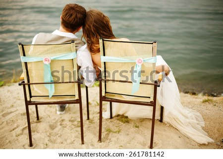 Romantic young newlyweds couple sitting near water on the beach, resting after wedding ceremony. Back view of a couple. - stock photo