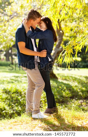 romantic young teenage coupe kissing in forest - stock photo
