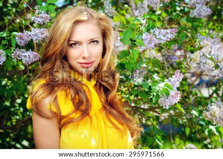 Romantic young woman in the spring garden among blooming lilac. - stock photo