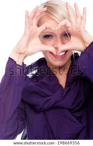 Romantic young woman making a heart gesture with her fingers around her eyes to signal her love and affection for a sweetheart or lover, isolated on white - stock photo