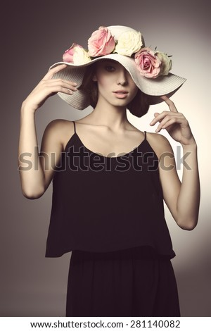 romantic young woman with black dress and big elegant hat with colorful flowers. Looking in camera in fashion pose  - stock photo