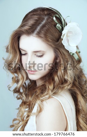 Romantic young woman with long curly blond hair looking down - stock photo