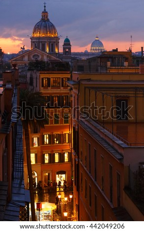 Rome City night illuminated view from top of Spanish Steps. Sant Ambrogio e Carlo al Corso basilica top and Saint Peter Basilica dome (behind), Italy.All people are unrecognizable. - stock photo
