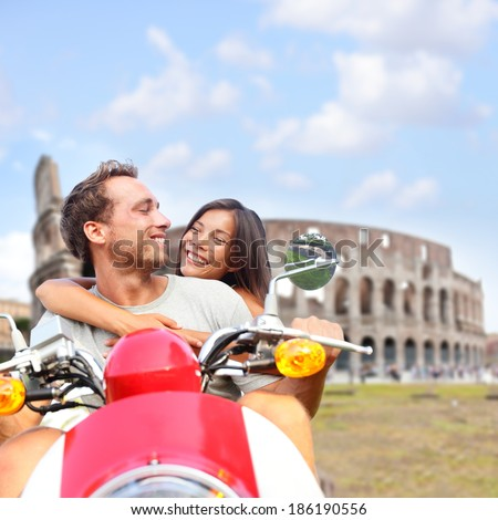 Rome couple on scooter by Colosseum, Italy. Romantic happy lovers driving scooter on honeymoon having fun in front of Coliseum. Love and travel concept with multiracial couple.