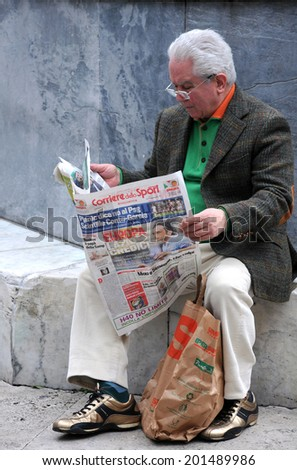 ROME, ITALY - APRIL 28, 2014: Aged man reads Corriere dello Sport newspaper  in the open air - stock photo